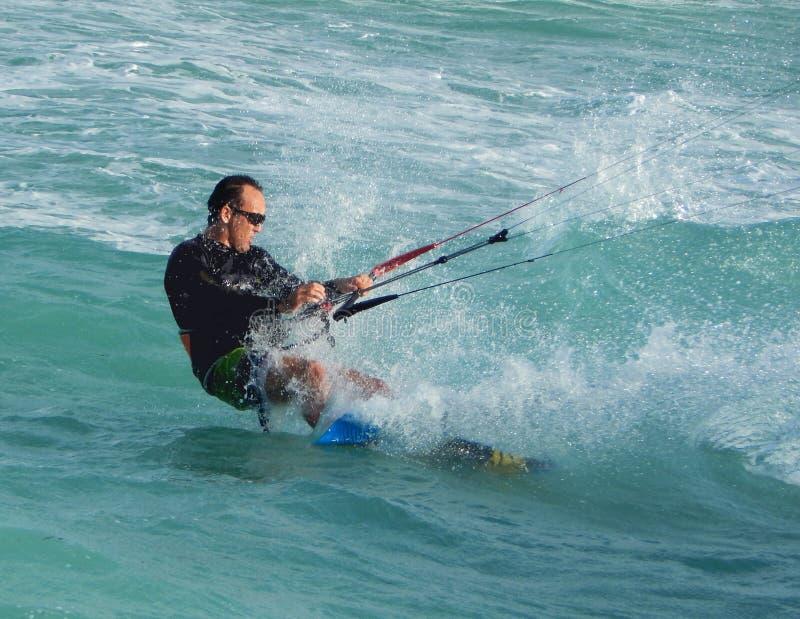 Пансионер змея занимаясь серфингом отрезки и брызги океана стоковое фото