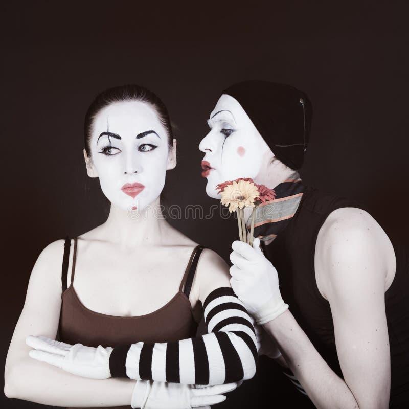 Пантомима пробует расцеловать женщину стоковое фото rf