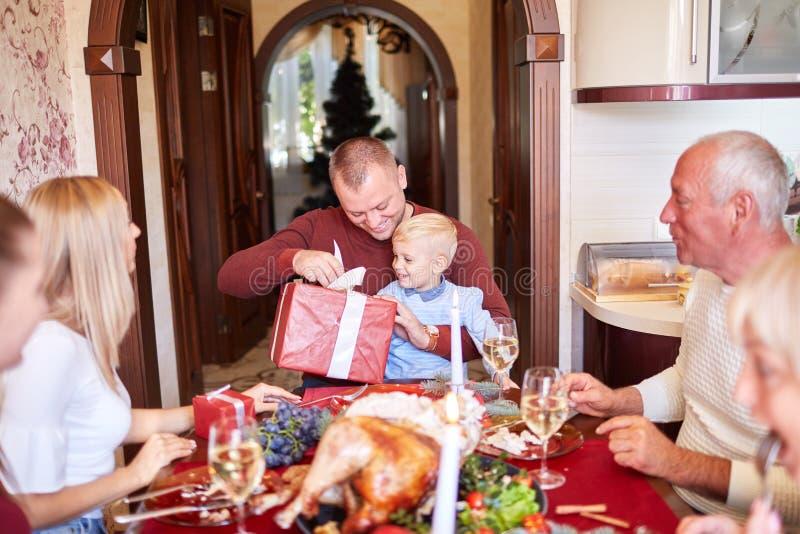 Папа давая красный подарок к маленькому сыну на festivebackground Концепция подарков на рождество семьи стоковая фотография rf