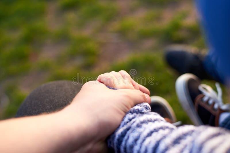 Папа держит руку его сына outdoors, родительская концепция любов стоковые изображения