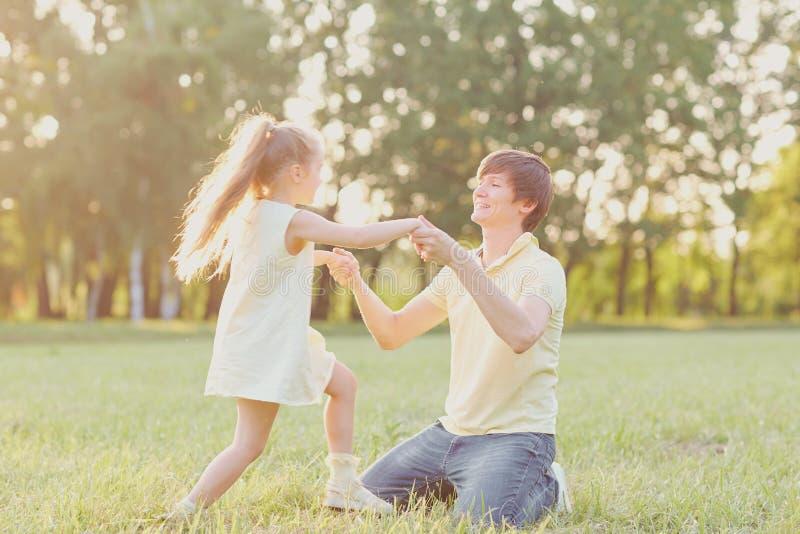 Папа играет с его дочерью дальше в парке стоковые фото