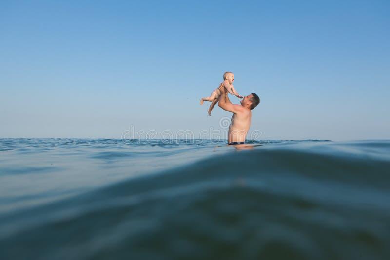 Папа играя с его дочерью в море стоковые изображения