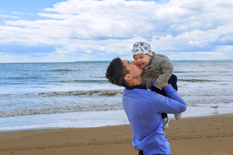 Папа играя с молодым сыном на пляже стоковое фото