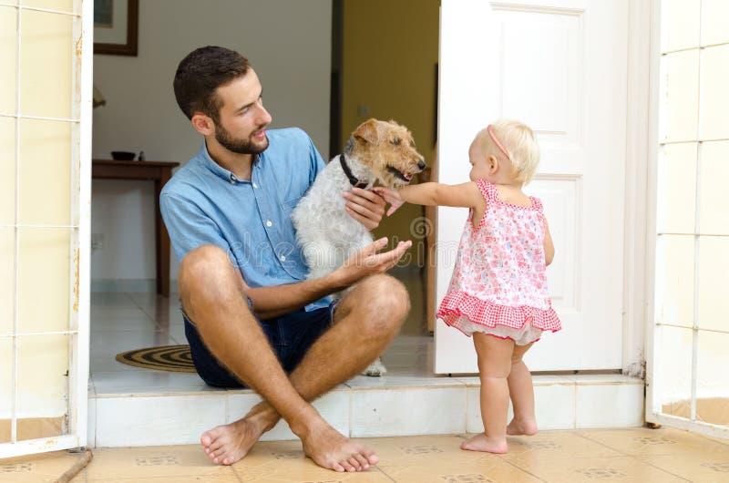 Папа и дочь и их собака Человек и девушка около ее дома на крылечке Рядом с ними их любимчик стоковое изображение rf