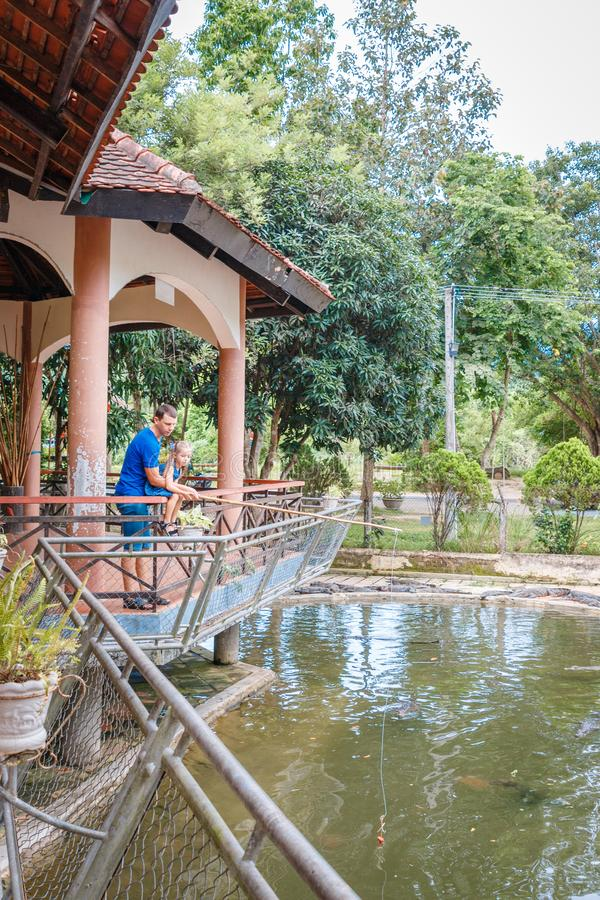 Папа и дочь кормили крокодилов, ферму крокодила, крокодилов будучи кормить цыпленка связанный к веревочке Залив Yang, Вьетнам стоковое изображение rf