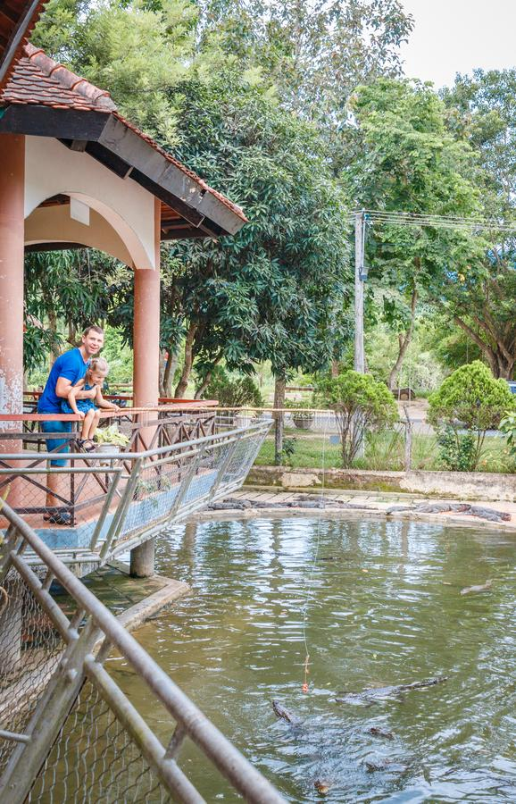 Папа и дочь кормили крокодилов, ферму крокодила, крокодилов будучи кормить цыпленка связанный к веревочке Залив Yang, Вьетнам стоковая фотография