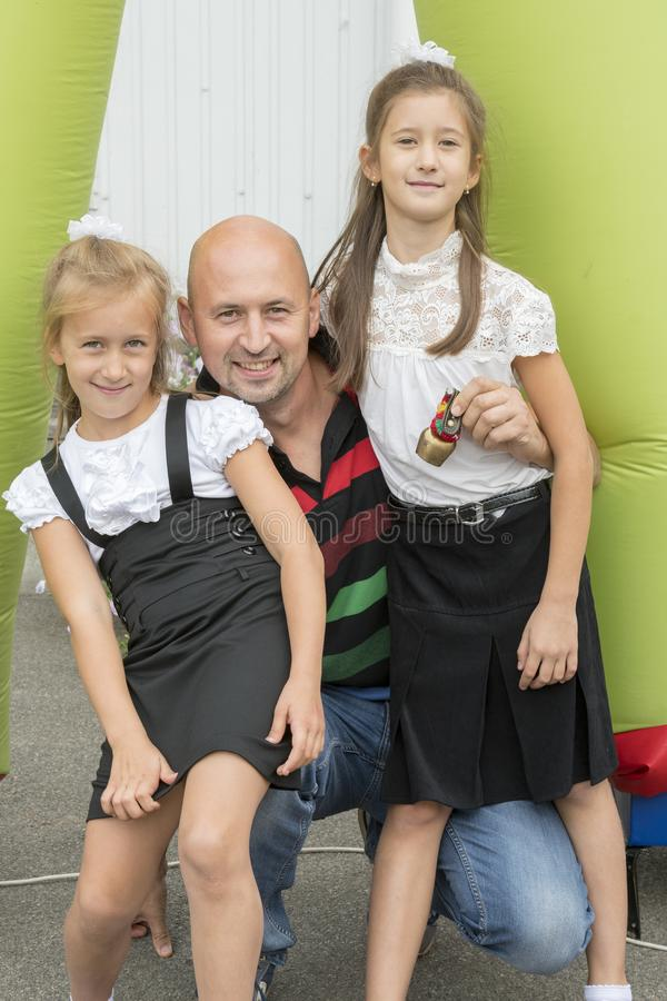 Папа и его дочери на школе 1-ого сентября Концепция влюбленности для детей и отцов Счастливые дочери с папой Вертикальный p стоковая фотография