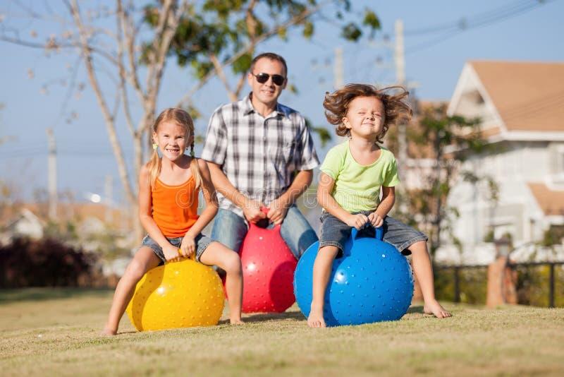 Папа и дети играя на лужайке стоковое изображение