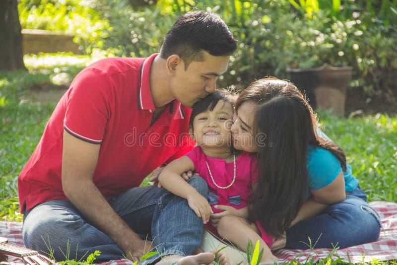 Папа и мама целуя их дочь стоковое фото