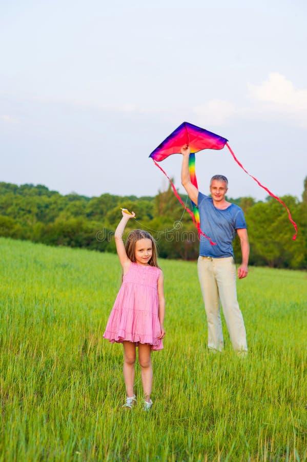 Папа и дочь летают змей стоковое изображение