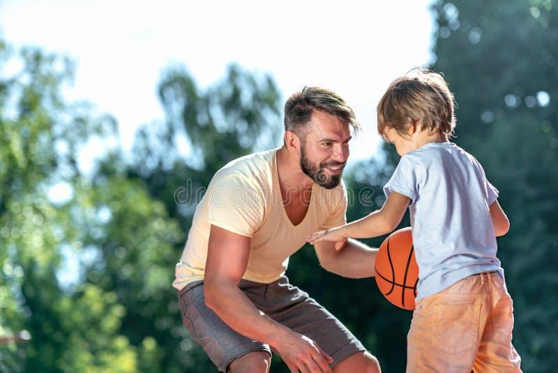Папа и сын играя баскетбол стоковая фотография