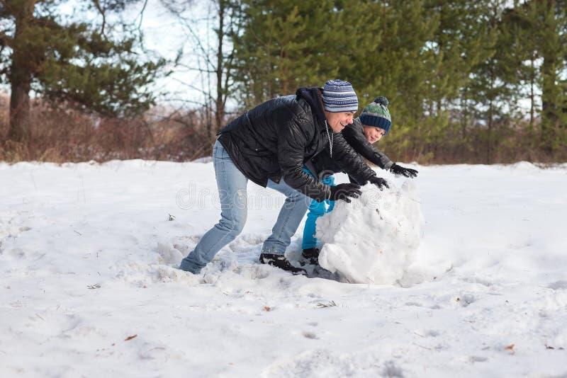Папа и сын играя в снеге стоковое изображение rf