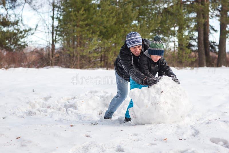 Папа и сын играя в снеге стоковое фото rf