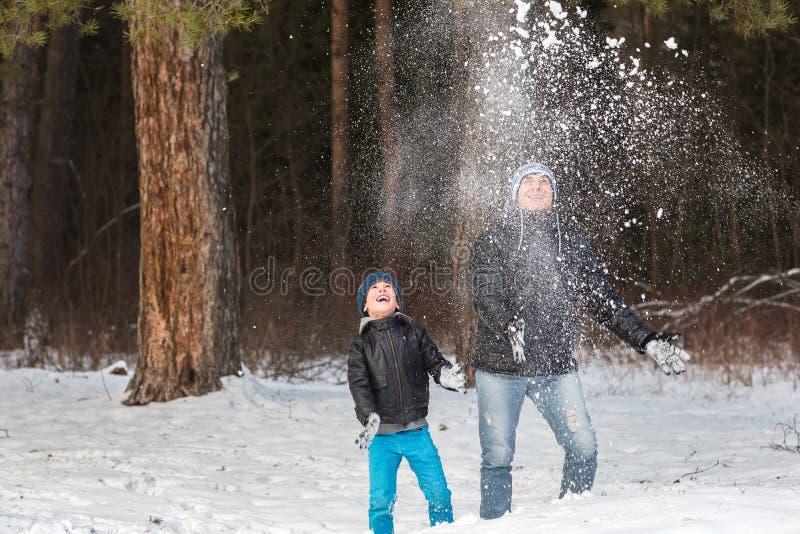 Папа и сын играя в снеге стоковые фотографии rf