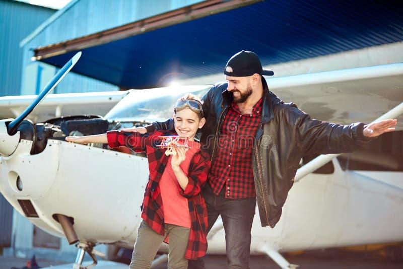 Папа и сын играя, претендующ самолеты, стоя с руками врозь как крылья стоковые фотографии rf