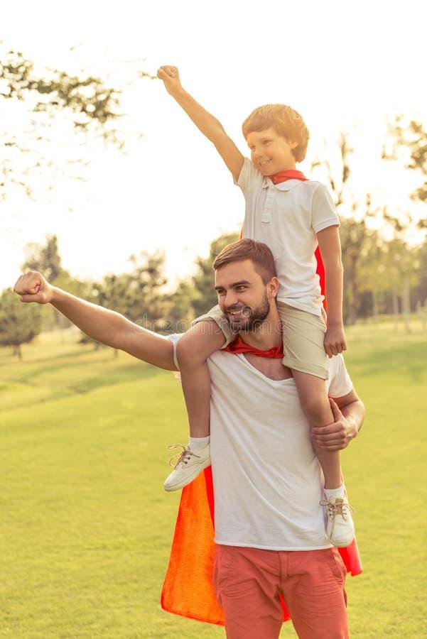 Папа и сын играя супергероев стоковые изображения