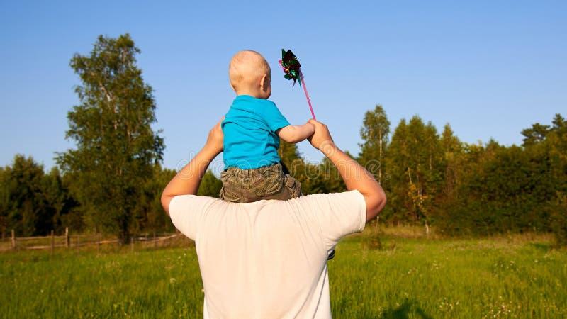 Папа и сын имея потеху в природе летом, отце держа его ребенка на его плечах с pinwheel, задним взглядом стоковые изображения rf