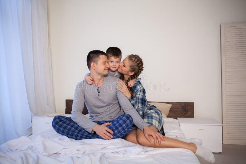 Папа и сын мамы в утре лежа на кровати дома стоковое изображение