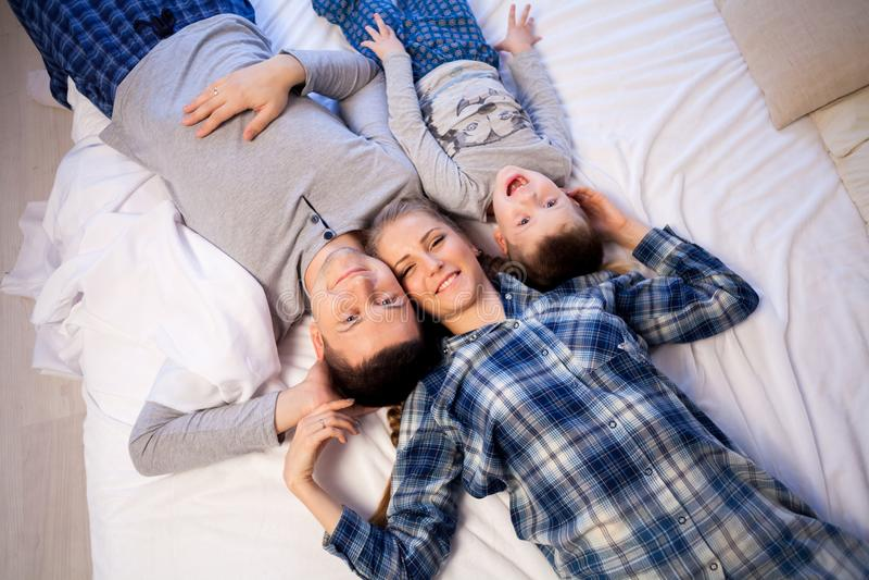 Папа и сын мамы в утре лежа на кровати дома стоковое фото