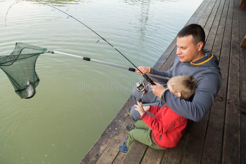 Папа и сын на рыбной ловле стоковое фото
