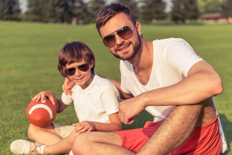 Папа и сын отдыхая outdoors стоковое фото rf