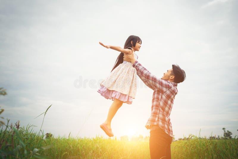 Папа нося его дочь с природой и солнечным светом, наслаждением стоковые изображения rf