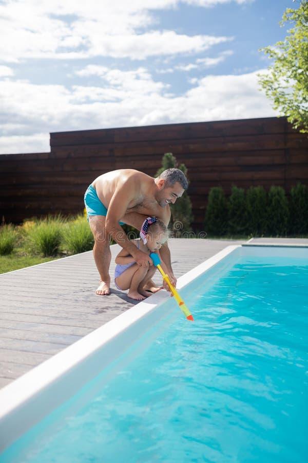 Папа помогая его милой девушке используя пистолет воды стоковые фотографии rf