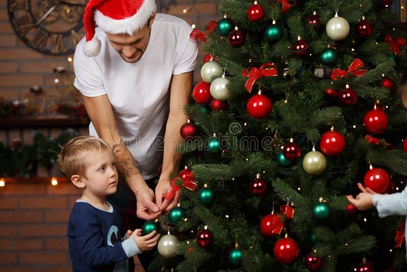 Папа, сын украшает рождественскую елку стоковые фото