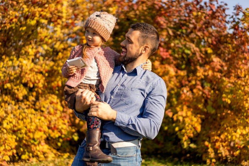 Папа с дочерью в любов идя в парк осени стоковые фотографии rf