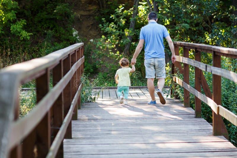 Папа с маленькими дочери лестницами вниз деревянными в парке стоковое изображение rf