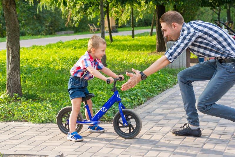 Папа улавливает его сына, который едет езда велосипеда в парке стоковая фотография