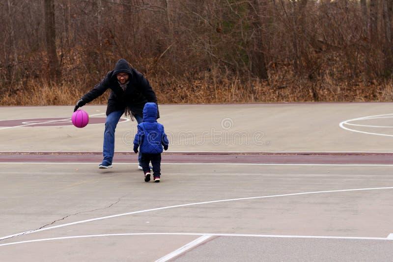 Папа уча его 2 летам сына для того чтобы сыграть парк баскетбола весной стоковые изображения rf