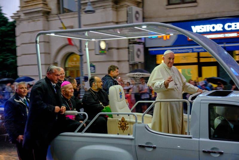 Папа Фрэнсис развевая к людям на Румынии от его папамобиля, поздно вечером с проливным дождем стоковое изображение