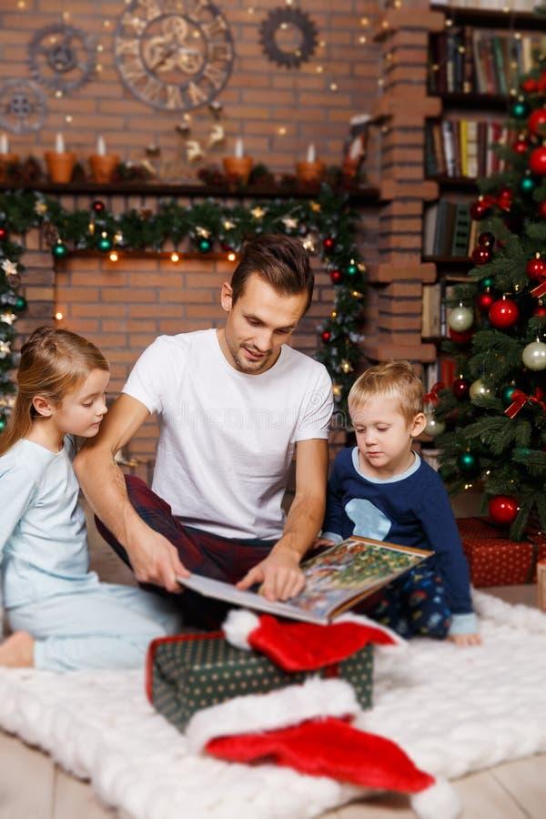 Папа читает книгу к детям стоковые фотографии rf