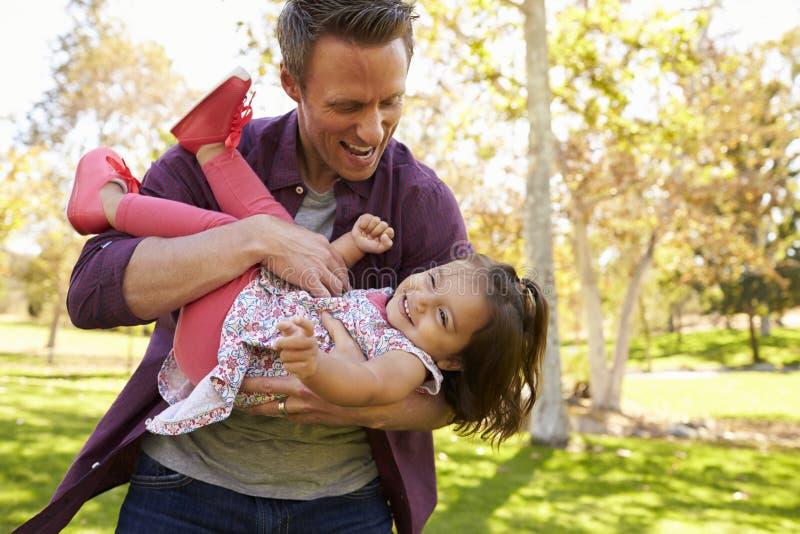 Папа cradling дочь малыша в его оружиях на парке стоковое изображение