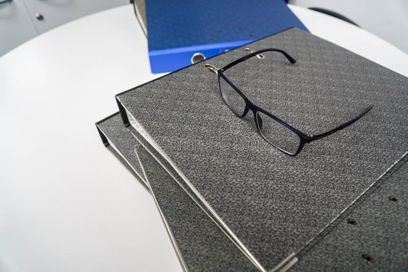 Папки дела со стеклами глаза на верхней части в рабочем месте стоковые фотографии rf