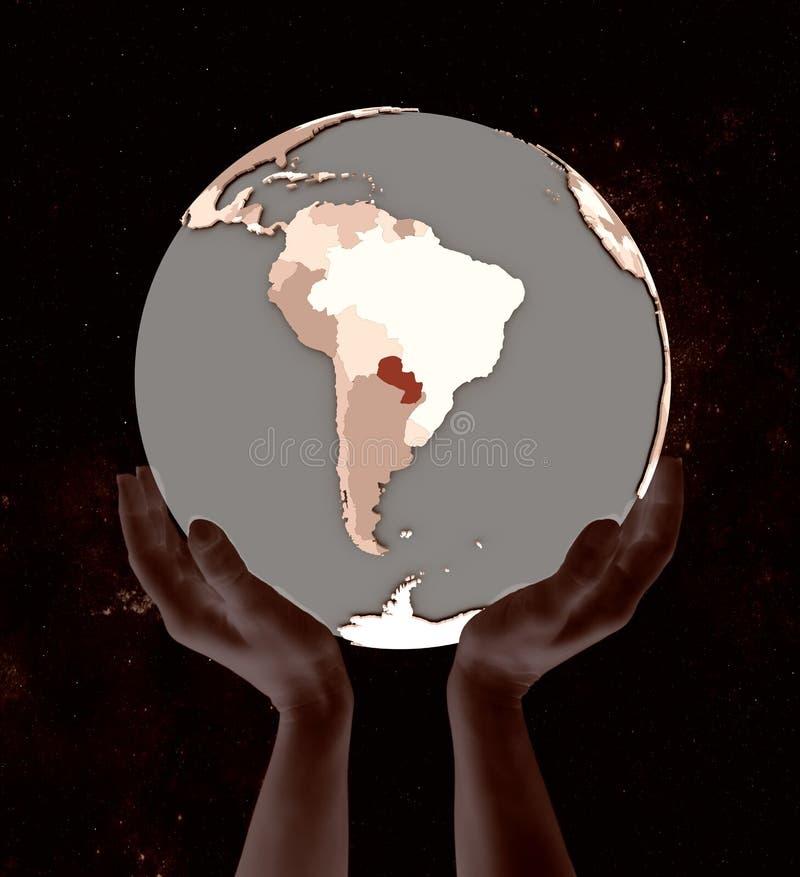 Парагвай на глобусе в руках стоковая фотография rf