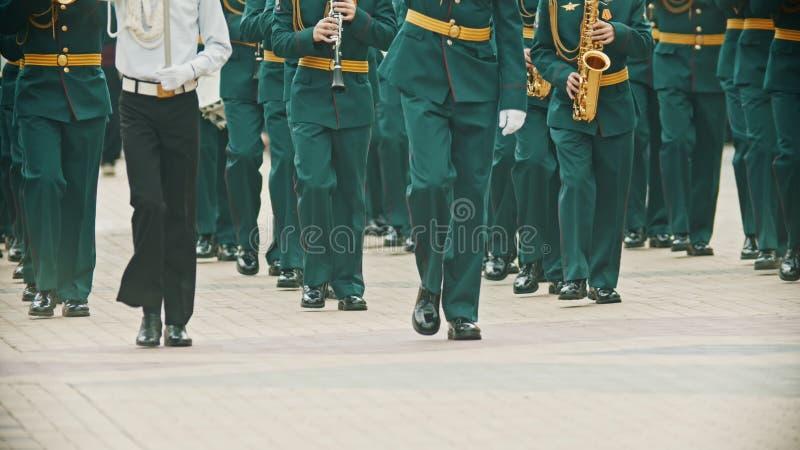 Парад ветряных инструментов - военные музыканты в зеленых костюмах маршируют на улице с музыкальными инструментами видеоматериал