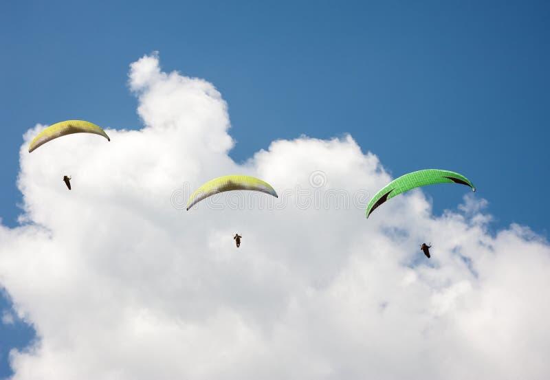3 параплана летая в голубое небо на фоне облаков стоковые изображения
