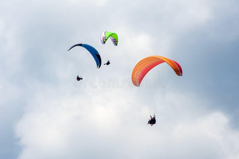 3 параплана летая в голубое небо на фоне облаков стоковые фотографии rf