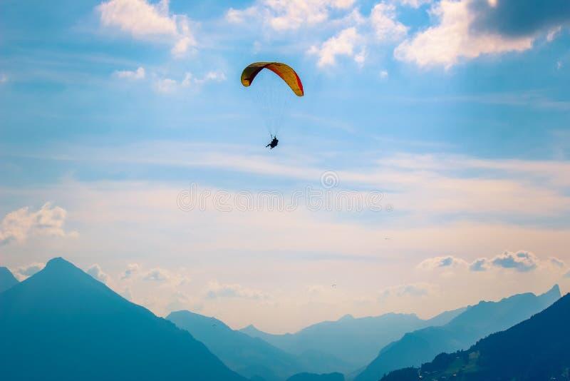 Парапланы летая над горами в Интерлакене, Швейцарии Силуэт швейцарских Альп Тандемный парапланеризм Рассветать, заход солнца стоковое изображение rf