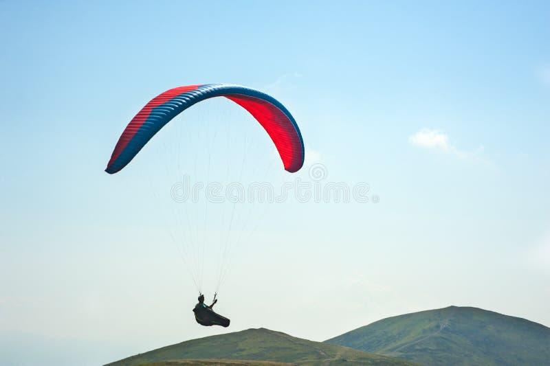Параплан летает над долиной горы на солнечный летний день P стоковые фото