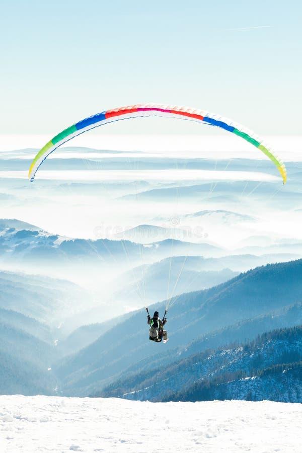 Парапланы запустили в воздух от снежного наклона горы стоковое фото rf