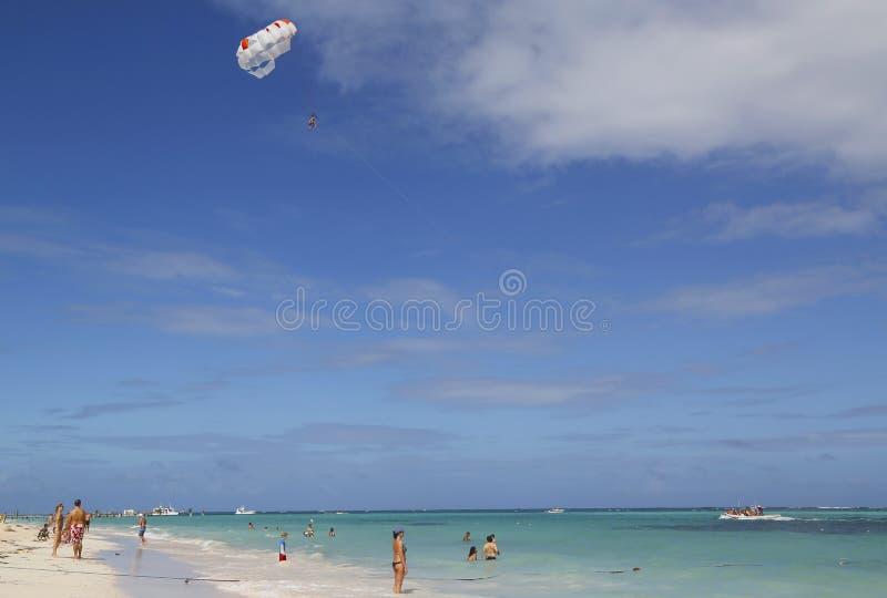 Парасейлинг в голубом небе над пляжем Bavaro в Punta Cana, Доминиканской Республике стоковые фотографии rf