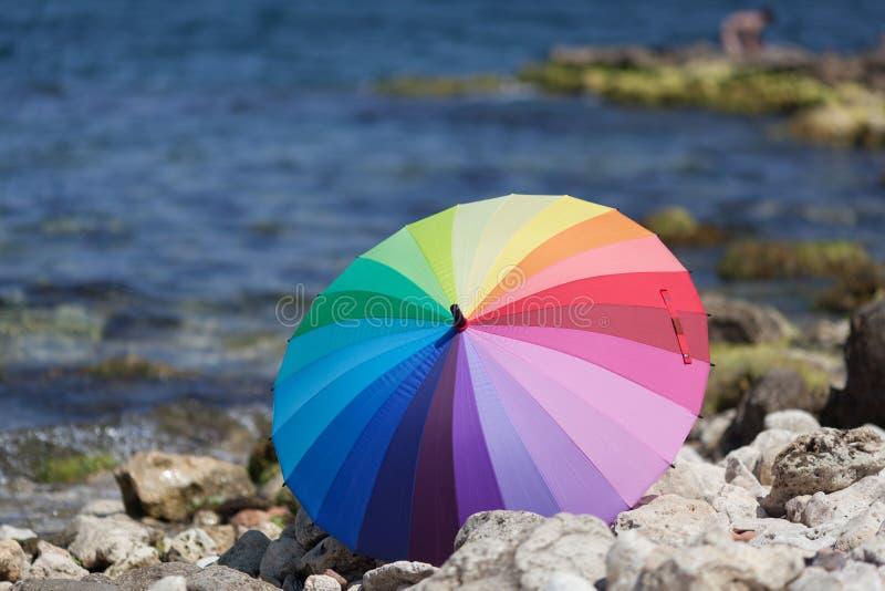 Парасоль радуги на прибрежных камнях стоковое фото rf