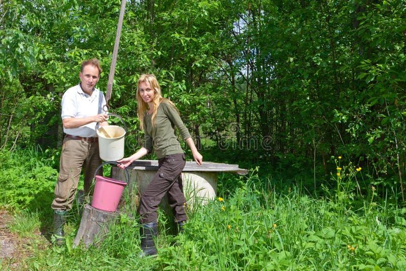 пара ведра счастливая льет добро воды стоковая фотография rf