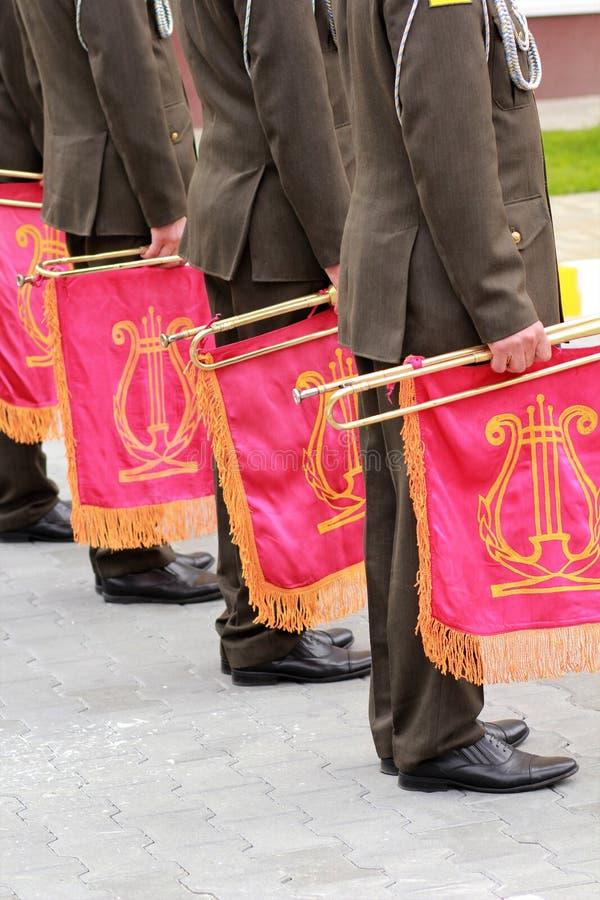 Парад воинского оркестра держа трубу музыкального инструмента с эмблемой революции и золотой лирой стоковое фото rf