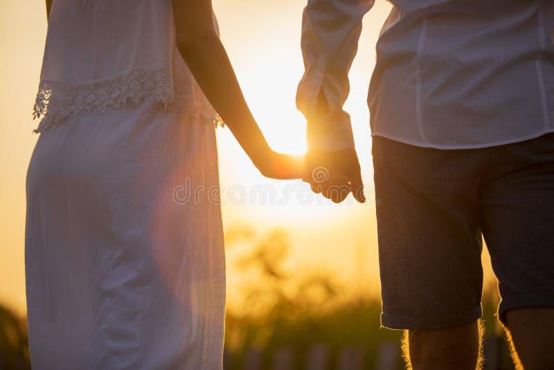 пара вручает заход солнца удерживания стоковая фотография