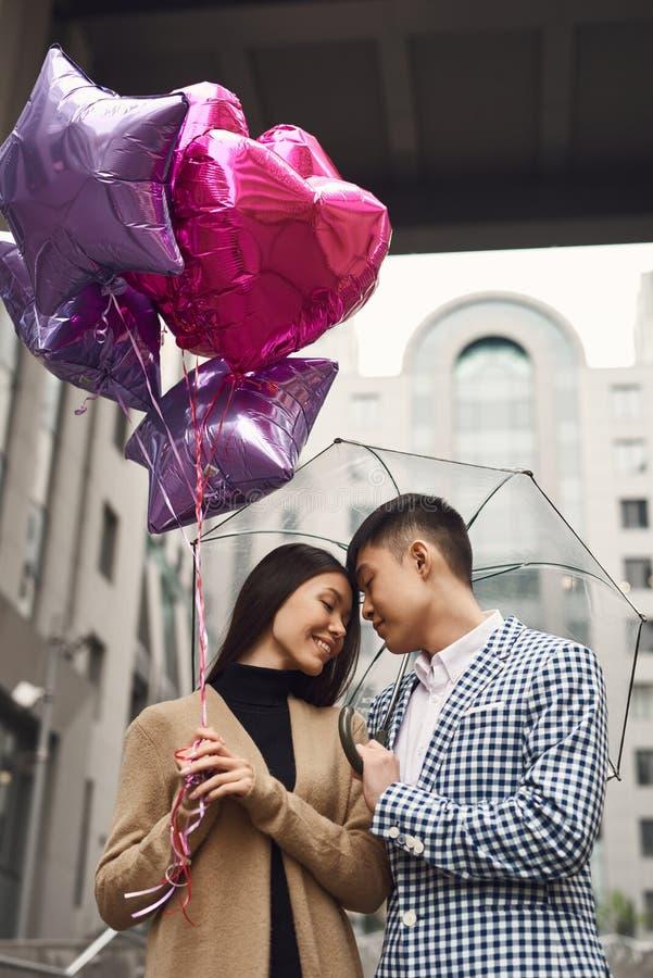 Пара в влюбленности под зонтиком с шариками гуляет вдоль переулка стоковое изображение