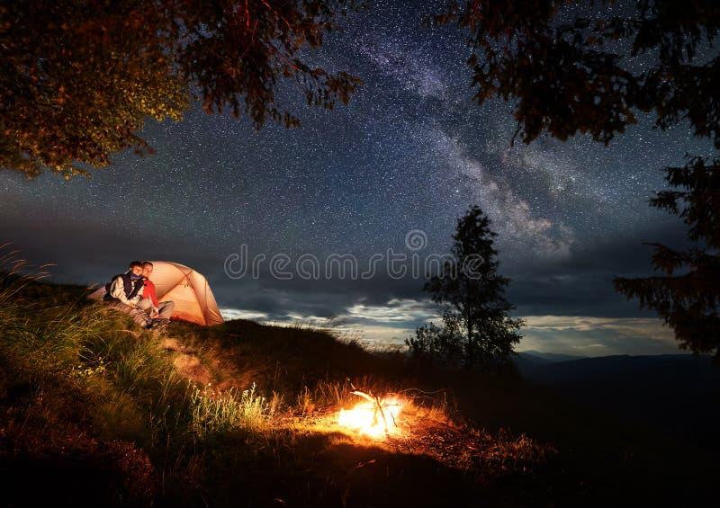 Пара в влюбленности сидит на холме около шатра наслаждаясь горящим огнем под ночным небом посыпанным с яркими звездами стоковое фото